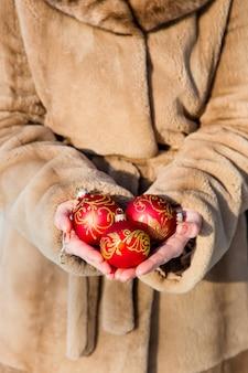 Женщина, одетая в шубу, держит в руках три красных новогодних шара крупным планом, концепция новогодняя открытка