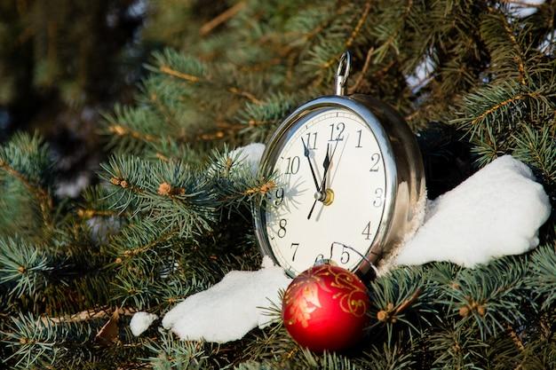 Красный елочный шар и часы на ели. концепция открытки новый год. копирование пространство