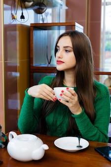 美しい若い女性はカフェでお茶を飲む