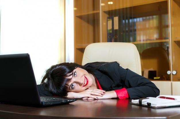 笑顔の女性がオフィスの机の上に彼女の頭を置く