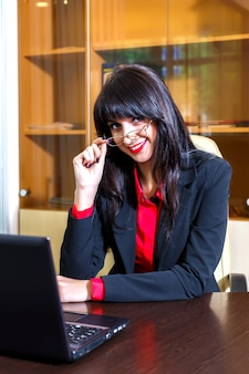 メガネで幸せな女は、オフィスのテーブルに座っています。