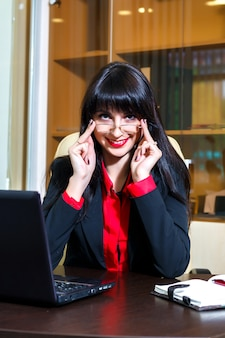 メガネで笑顔の女性がオフィスのテーブルに座っています。