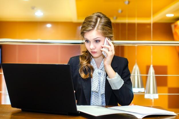 ノートパソコンでカフェに座っていると携帯電話で話している若い女の子