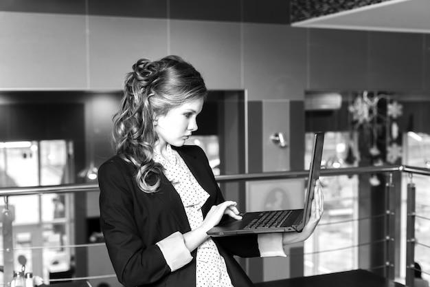 カフェに立っているとラップトップに取り組んでいる若い美しい女性