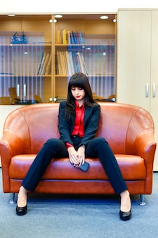 ソファの上のオフィスに座っているスーツで素敵な思いやりのある実業家