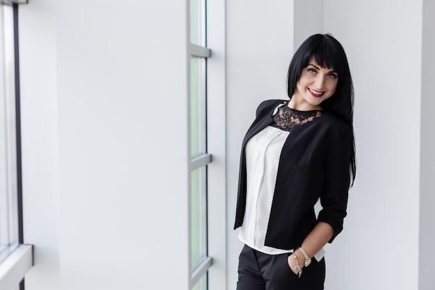 Молодая привлекательная счастливая женщина брюнетки оделась в черном деловом костюме, стоящем около окна в офисе, улыбаясь, смотря на камеру.