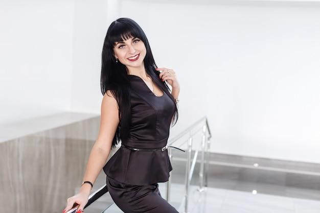Молодые довольно счастливая брюнетка женщина, одетая в черный деловой костюм с короткой юбкой, стоит у белой стены в офисе, опираясь на перила, улыбаясь, глядя в камеру.