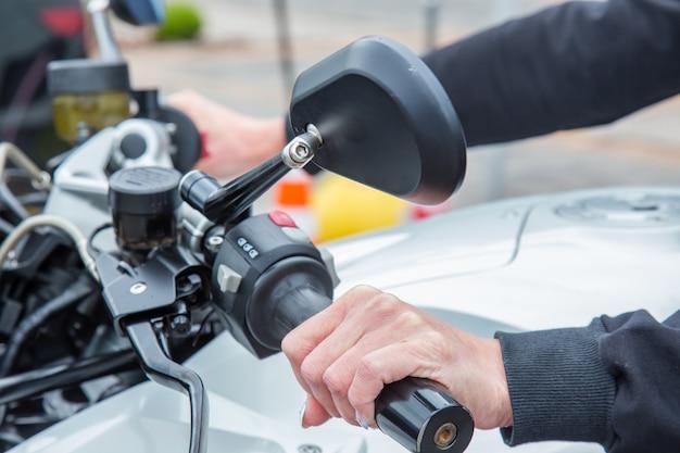 Женская рука на ручке регулировки скорости гоночного мотоцикла