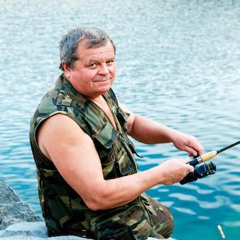 夏の日の川沿いの釣り竿を持つ古い漁師の笑顔