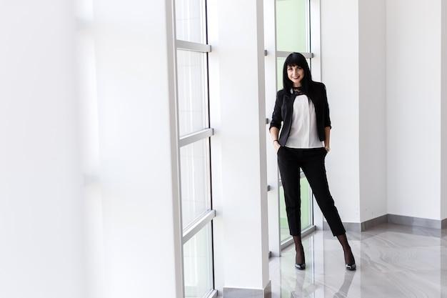 Молодая привлекательная счастливая женщина брюнетки оделась в черном деловом костюме