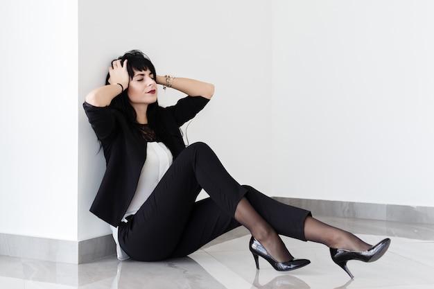 Красивая уставшая молодая женщина в черном деловом костюме сидит на полу в офисе