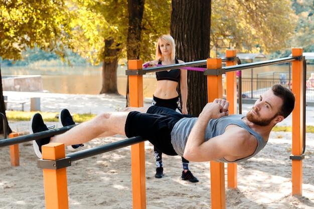 スポーティな白人の若いカップルは、屋外の公園でトレーニングする前にウォーミングアップしています。