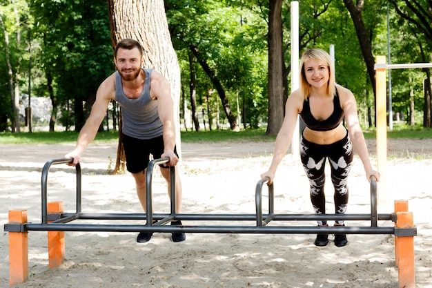 若い陽気な女性とひげを生やした男が公園で腕立て伏せの演習を行います。