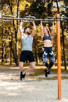 陽気な少女とひげを生やした男が秋の日に公園でクロスバーのプルアップ運動を行います。