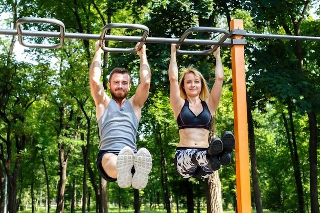 若い陽気な女性とひげを生やした男が公園でクロスバーでプルアップ演習を行います。