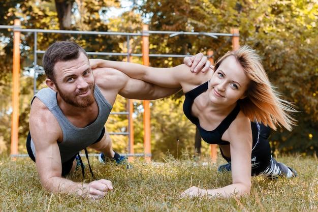 Молодая белокурая девушка и бородатый человек делая доску тренировки на солнечный день осени в парке.