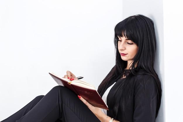 オフィスの床に座っている若い美しい深刻なブルネットの女性は、ノートに書き込みます