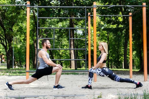 Спортивная блондинка и бородатый мужчина разминается перед тренировкой в парке на открытом воздухе.