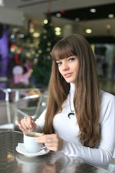 クリスマスツリーの背景にスーパーマーケットでコーヒーカップを持つ若い女性