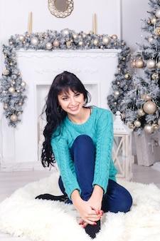 クリスマスの装飾のあるリビングルームに座っている若い女性