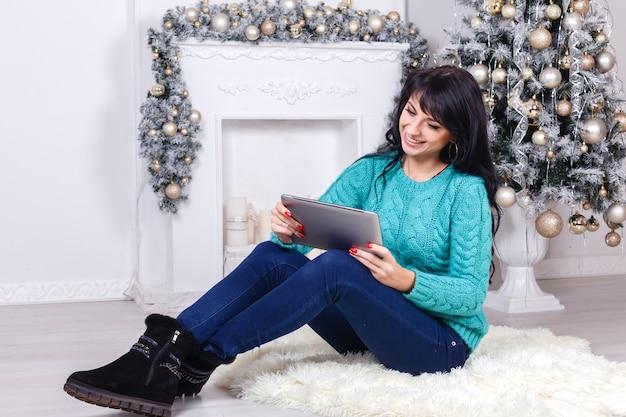 Красивая девушка сидя внутри помещения в украшении рождества держа белую таблетку пк.