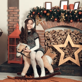 クリスマス装飾部屋でおもちゃの馬の上に座って長い髪の幸せな小さなブルネットの少女。