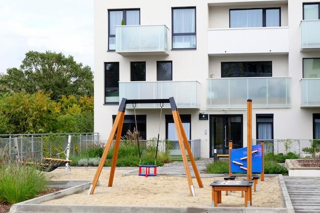 Детская площадка с гамаком и качелями в уютном дворе современного жилого района.