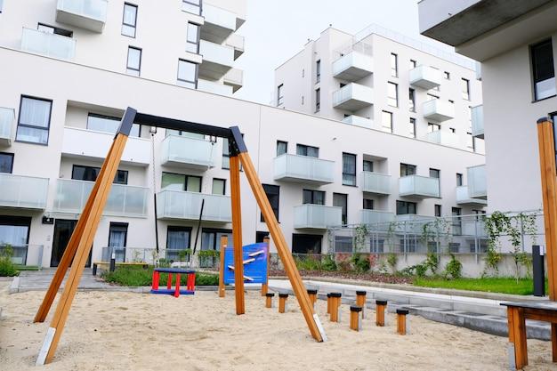 Детская площадка с качелями в уютном дворе современного жилого района.