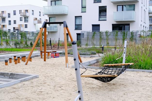 モダンな住宅街の居心地の良い中庭にある子供の遊び場でハンモックとスイングをお楽しみください。