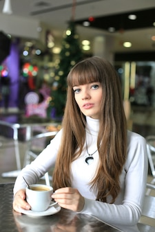 クリスマスツリーの背景にショッピングセンターでコーヒーのカップを持つ少女