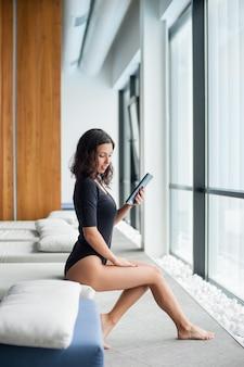 大きな窓の近くの白いラウンジャーでの女性