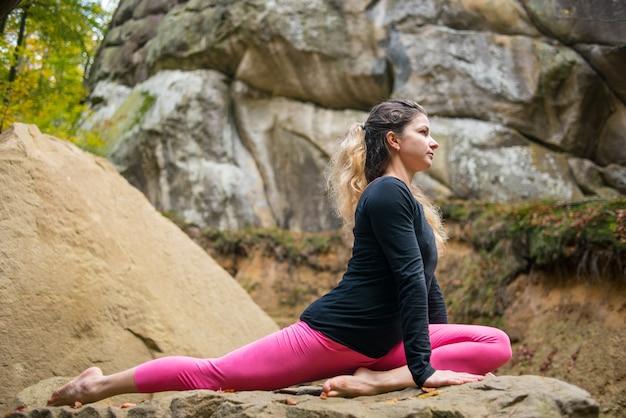 スポーティなフィット女性は自然の中でボルダーでヨガを練習しています