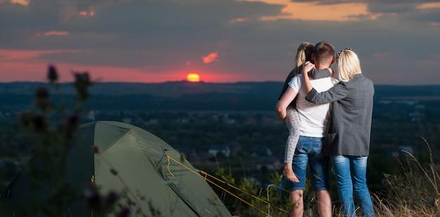 丘の上のキャンプテントの近くの家族