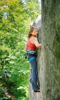 Красивая женщина альпинист, восхождение на крутой скале с веревкой