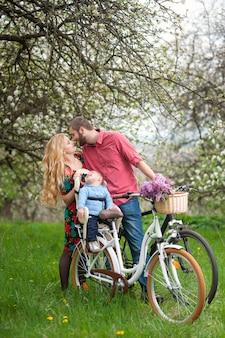 春の庭で自転車に乗って若い家族