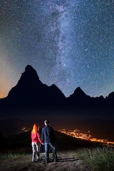 ロマンチックなカップル - 女の子と男が手を取り合って、丘の上に立っていると夜に信じられないほど美しい星空を楽しんでいます。