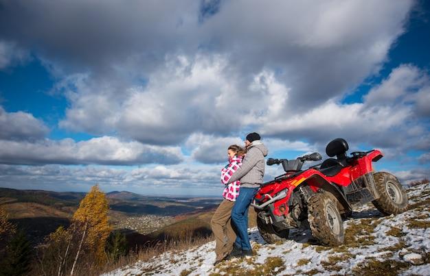 青い空の下の山の斜面に赤いクワッドバイクの近くの女性を抱き締める男