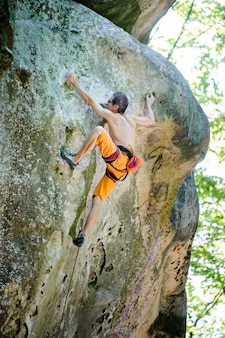 岩が多い壁にロープで登山男性ロック・クライマー