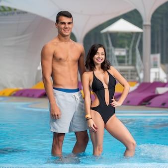 幸せなアスレチック男と背景をぼかした写真の高級マウンテンリゾートのスイミングプールのそばの完璧な図を持つ少女