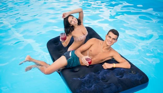 スイミングプールのマットレスの上に浮かぶ美しいペア、カクテルを飲む、夏休みに楽しんで