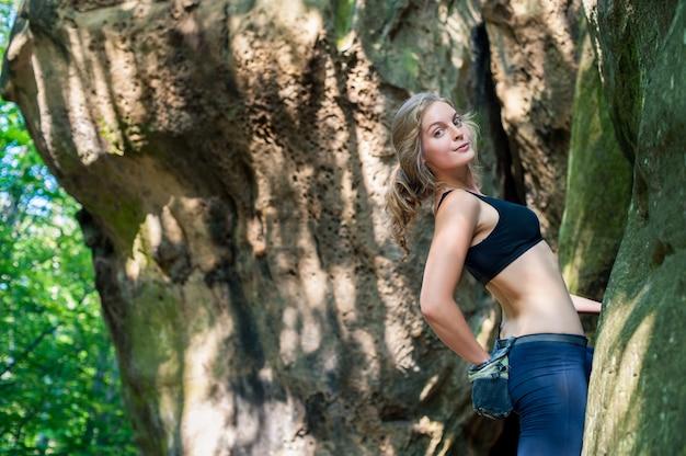 屋外の大きな岩に登る若い女性