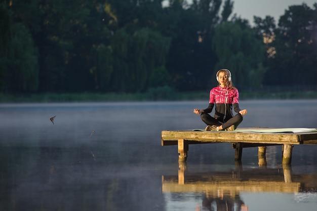 川の自然の中で瞑想の女性。ヨガ