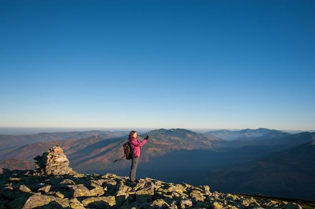 美しい少女は山で彼女のスマートフォンで写真を撮る