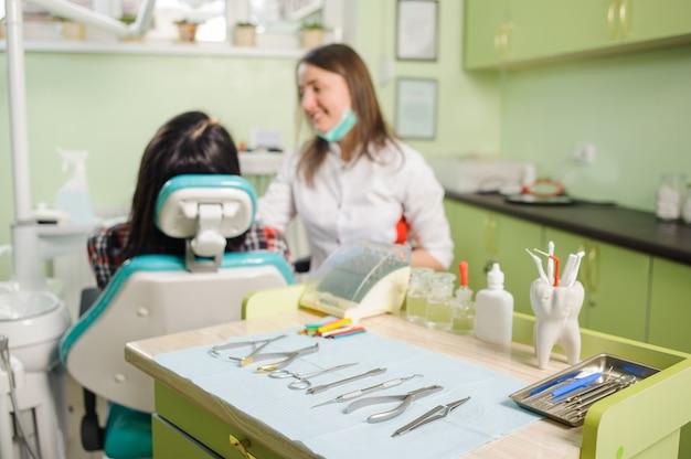 メスの患者と歯科医院で働く女性歯科医