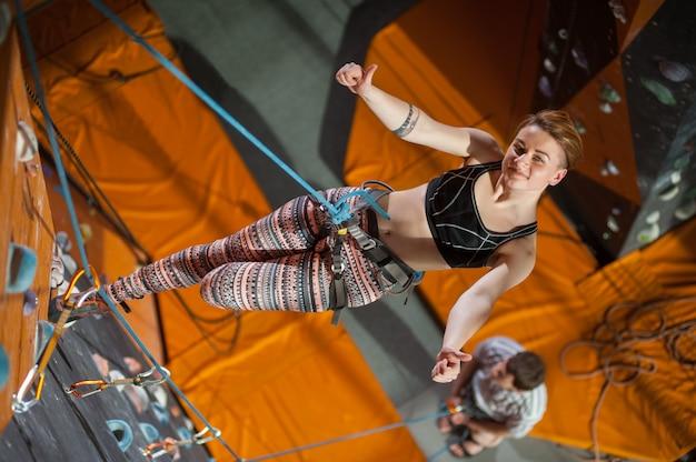 女性の登山家は屋内ロッククライミングウォールに登っています