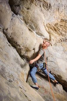 男性のリードクライマーが山の中の大きな岩に登る