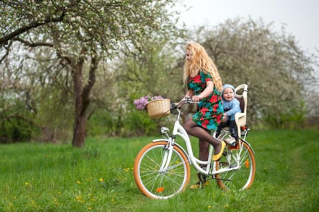 Блондинка женщина езда городской велосипед с ребенком в кресле велосипеда