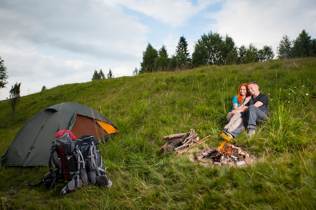 Пара сидит на зеленой траве возле палатки и костра