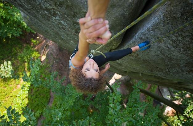 女性クライマーが山の頂上に達するのを助けるクライマー
