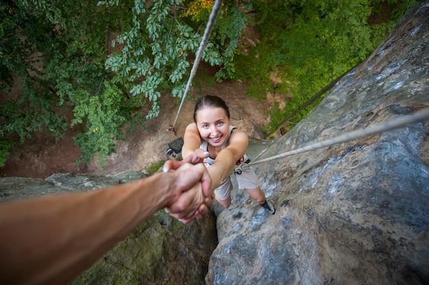 ロッククライマーが山の頂上に到達するために女性の登山者を助ける